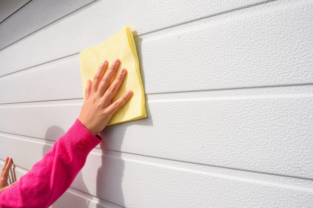 Hand using a microfibre cloth to clean garage door | Garage Door Maintenance Tips